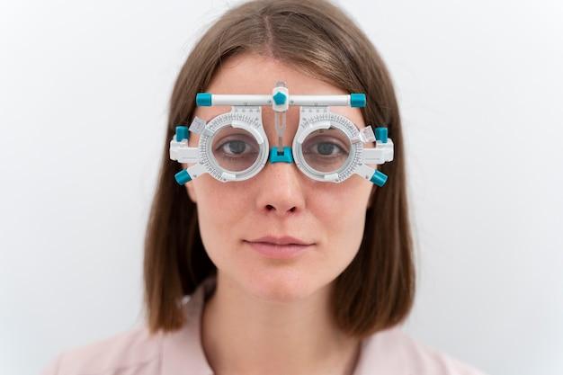 Kobieta sprawdzająca dioptrie specjalnym sprzętem do soczewek