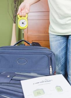 Kobieta sprawdzająca wagę bagażu podręcznego za pomocą wagi stalowej zgodnie z ograniczeniami tanich linii lotniczych