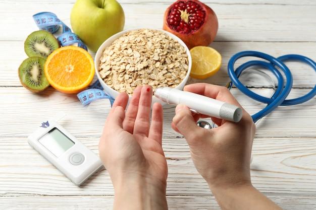 Kobieta sprawdzanie poziomu cukru we krwi na tle z akcesoriami dla diabetyków
