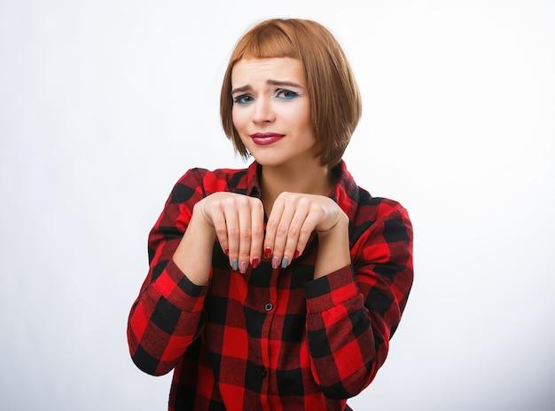 Kobieta sprawia, że workowanie znak rękami. portrety młodej kobiety z różnymi szczęśliwymi emocjami. koszula w kratkę i rude włosy. żałosne emocje.