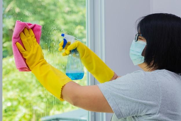 Kobieta spryskuje i wyciera szkło