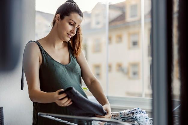 Kobieta sprząta bałagan w domu. przemyślana młoda kobieta z kucykiem starannie przygotowała suche i czyste pranie w ciągu dnia na tarasie. sprzątanie domu, sprzątanie, prace domowe