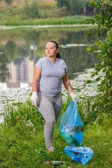 Kobieta sprząta śmieci na wysypisku w parku.