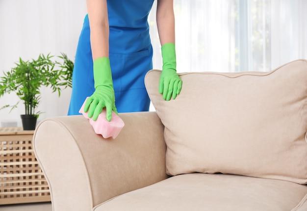 Kobieta sprzątająca kanapę z gąbką w domu