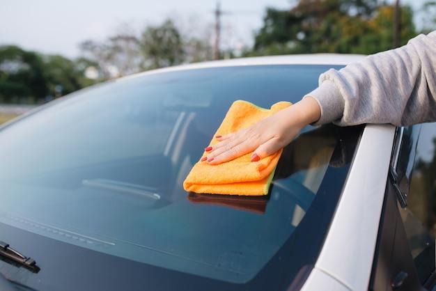 Kobieta sprzątająca samochód ściereczką z mikrofibry, koncepcja car detailingu (lub valeting)