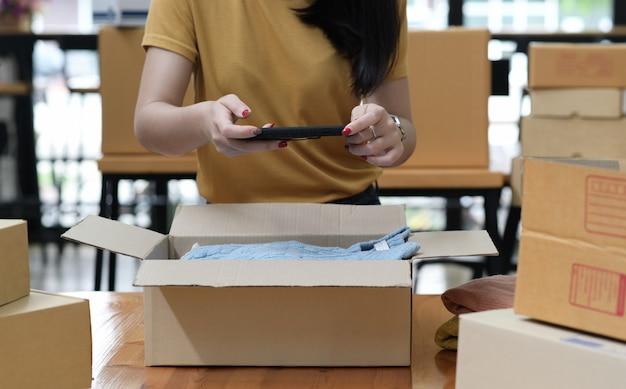 Kobieta sprzedająca produkt online robi smartfonem zdjęcie produktu w pudełku.