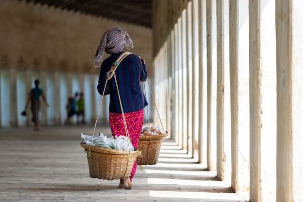 Kobieta sprzedaje owoce z koszy