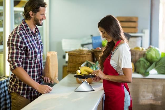 Kobieta sprzedawca pomiaru bananów z wagą przy kasie
