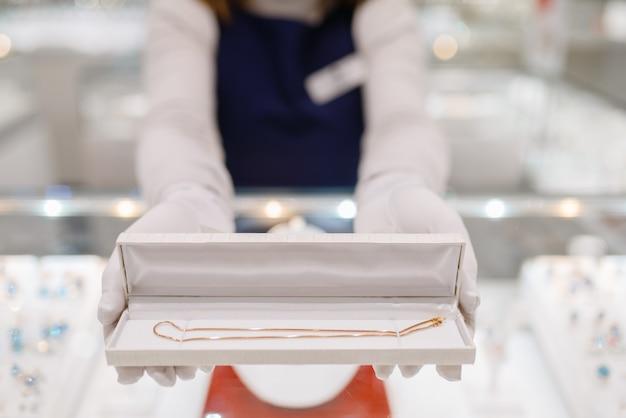 Kobieta sprzedawca ręce ze złotą bransoletką w etui