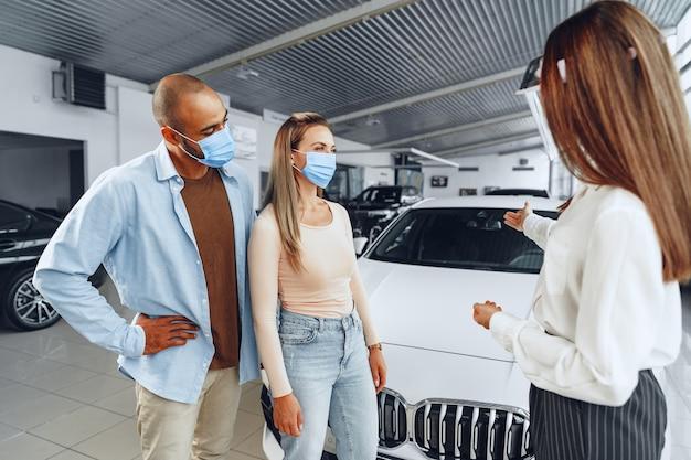 Kobieta sprzedawca samochodów konsultuje kupujących noszących medyczną osłonę twarzy. koncepcja wymagań pracy koronawirusa