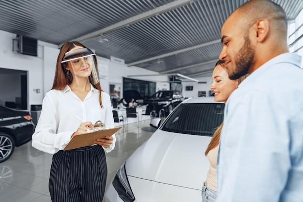 Kobieta sprzedawca samochodów konsultuje kupujących noszących medyczną osłonę twarzy