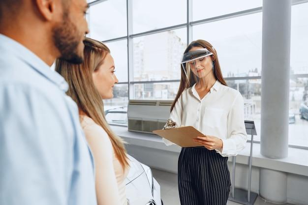 Kobieta sprzedawca samochodów konsultuje kupujących noszących osłonę twarzy