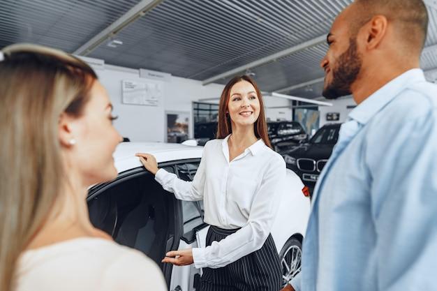 Kobieta sprzedawca samochodów wyjaśnia kupującym cechy swojego nowego samochodu w salonie samochodowym