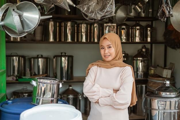 Kobieta sprzedawca uśmiechając się skrzyżowanymi rękami w sklepie agd
