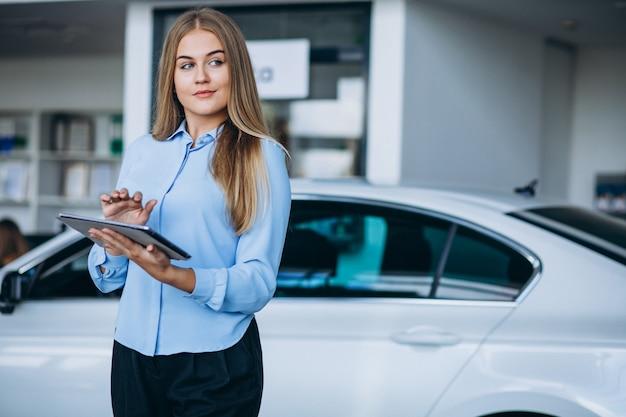 Kobieta sprzedawca w salonie samochodowym samochodem