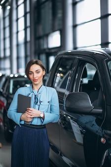Kobieta sprzedawca w salonie samochodowym