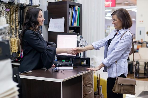 Kobieta sprzedawca w sklepie tekstylnym z klientem