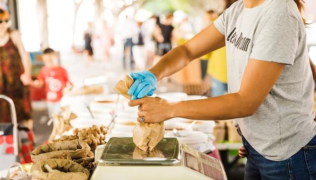 Kobieta sprzedawcy pakowania jedzenie dla jej klienta w rynku