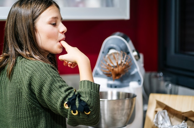 Kobieta Ssie Posmarowane Czekoladą Palce W Domowej Kuchni Premium Zdjęcia