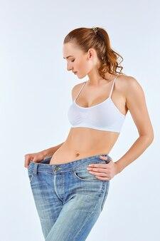 Kobieta stała się chuda i nosi stare dżinsy na białym tle koncepcja zdrowego