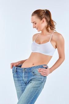 Kobieta stała się chuda i ubrana w stare dżinsy na białym tle. koncepcja zdrowego stylu życia i piękna