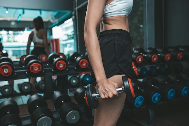 Kobieta stała trzymając hantle na udzie na siłowni.