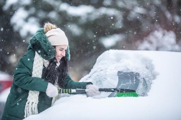 Kobieta stara się zeskrobać lód i śnieg z zaśnieżonego samochodu na parkingu.