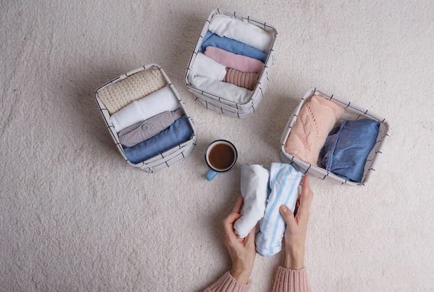 Kobieta starannie składa ubrania i wkłada je do koszy i pudełek. minimalizm w stylu skandynawskim.