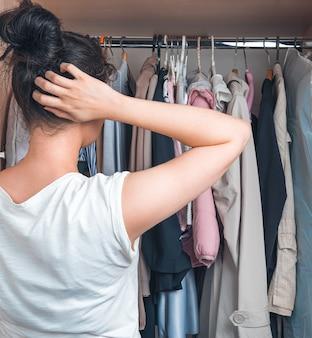 Kobieta starannie wybiera, w co się ubrać. pojęcie życia domowego.