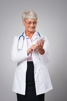 Kobieta starszy lekarz z mądrze telefonem
