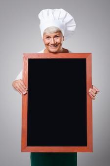Kobieta starszy szef kuchni z menu