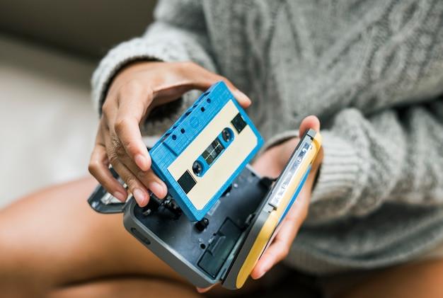 Kobieta stawia kasetę w odtwarzaczu kasetowym