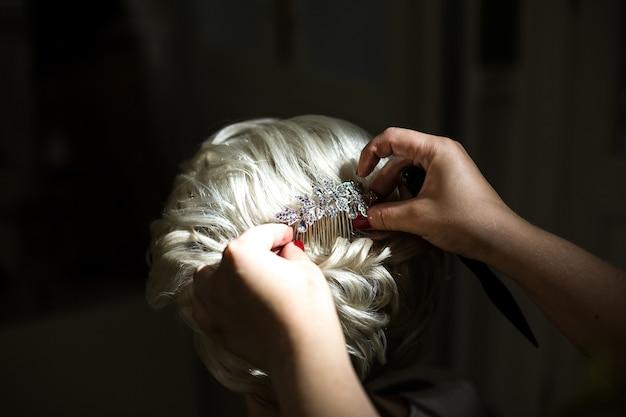 Kobieta stawia kryształową spinkę w blond włosach panny młodej