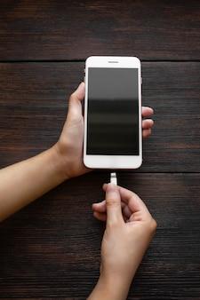 Kobieta stawia na ładowanie białego telefonu na ciemnym drewnianym stole