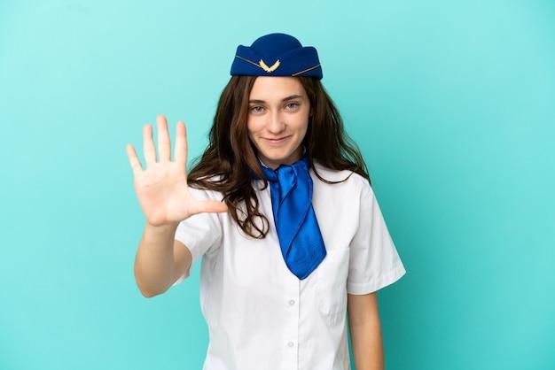 Kobieta stewardesa samolotu na białym tle na niebieskim tle licząc pięć palcami