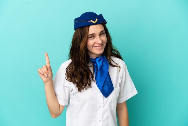 Kobieta stewardesa samolotu na białym tle na niebieskim tle pokazująca i unosząca palec na znak najlepszych