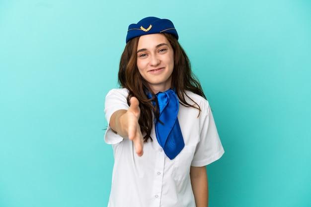 Kobieta stewardesa samolotu na białym tle na niebieskim tle, ściskając ręce, aby zamknąć dobrą ofertę