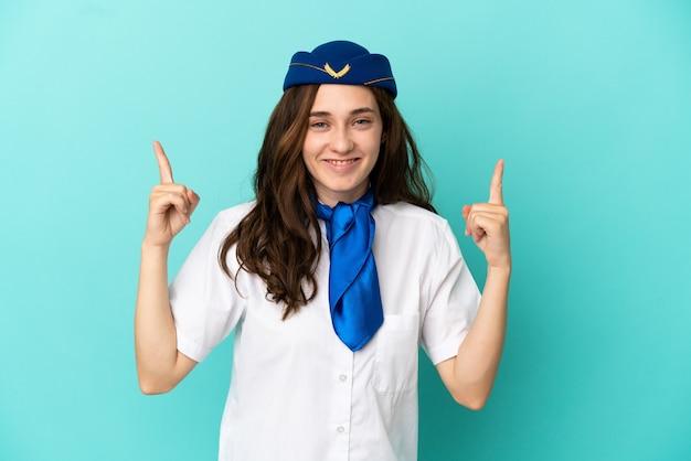 Kobieta stewardesa samolotu na białym tle na niebieskim tle wskazująca świetny pomysł