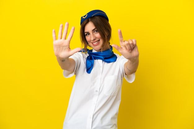Kobieta stewardesa samolotu na białym tle na żółtym tle licząc siedem palcami