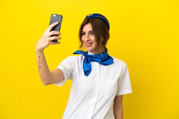 Kobieta stewardesa samolotu na białym tle na żółtym tle robi selfie