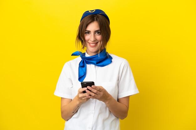 Kobieta stewardesa samolotu na białym tle na żółtym tle wysyłająca wiadomość za pomocą telefonu komórkowego