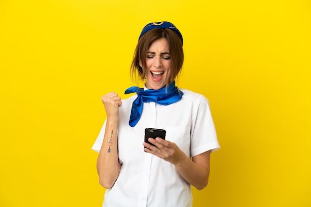 Kobieta stewardesa samolotu na białym tle na żółtym tle z telefonem w pozycji zwycięstwa