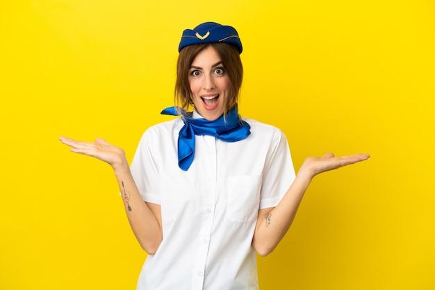 Kobieta stewardesa samolotu na białym tle na żółtym tle ze zszokowanym wyrazem twarzy