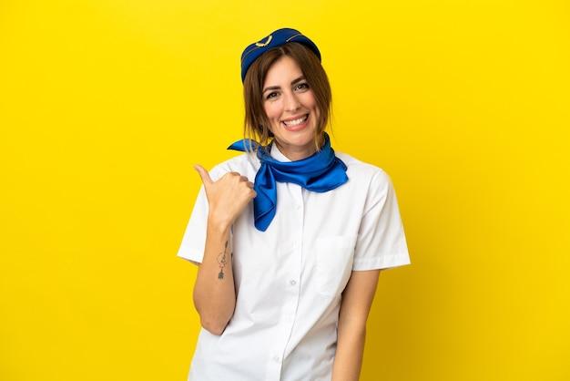 Kobieta stewardesa samolotu odizolowana na żółtym tle wskazująca na bok, aby zaprezentować produkt