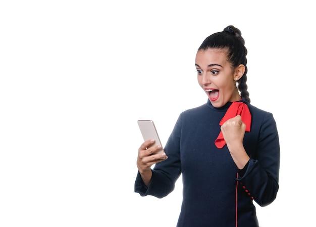 Kobieta stewardessy używa swojego telefonu komórkowego i odbiera dobre wieści