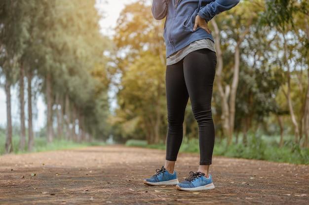 Kobieta stoi, aby oddychać naturalnym powietrzem po jogging.nature park. koncepcja zdrowego i stylu życia.