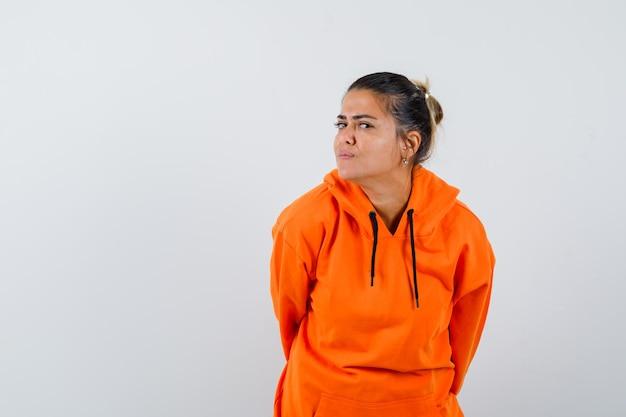 Kobieta stoi, aby wyraźnie słyszeć w pomarańczowej bluzie z kapturem i wygląda na zaciekawioną