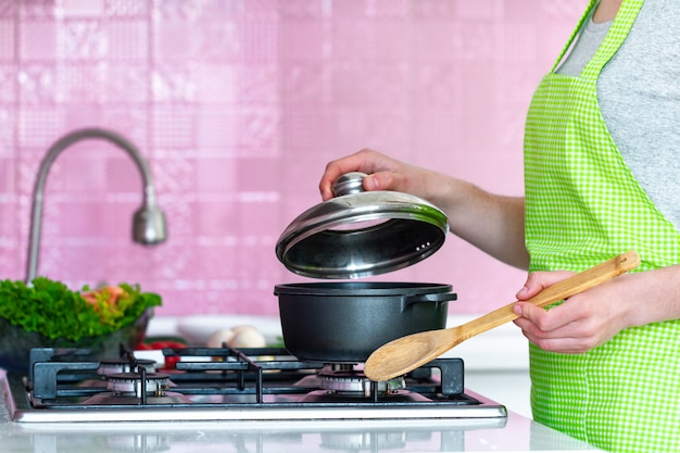 Kobieta stoi blisko kuchenki i kulinarnej polewki w kuchni w domu w fartuchu. gotowanie dla rodziny na obiad. czysta zdrowa żywność i prawidłowe odżywianie.