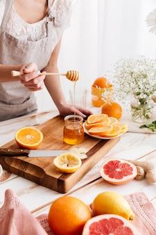 Kobieta stoi blisko stołu z cytrusami i trzyma miód.