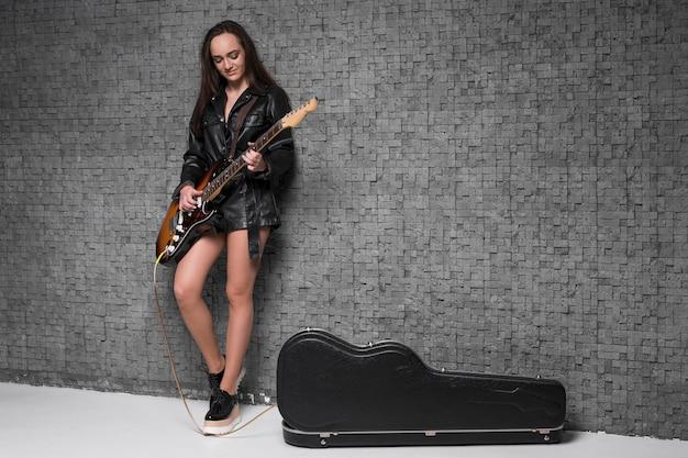 Kobieta stoi i gra na gitarze